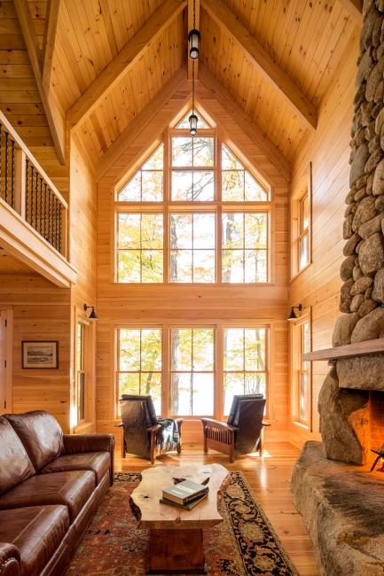 Stone fireplace, wood beam ceiling, large window bay, nickel gap pine walls