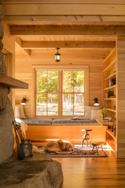 post and beam ceiling, pine board walls, stone fire place, dog laying in sun, reading nook