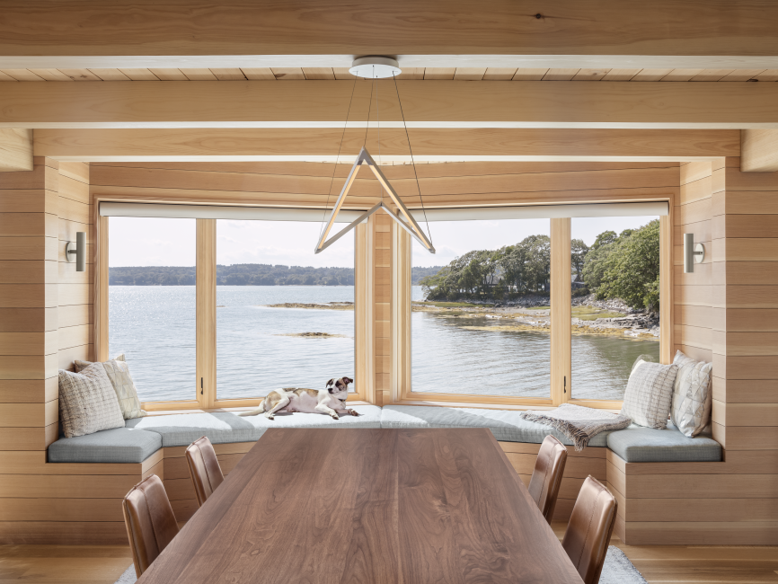 Dining table with views out bay windows to ocean