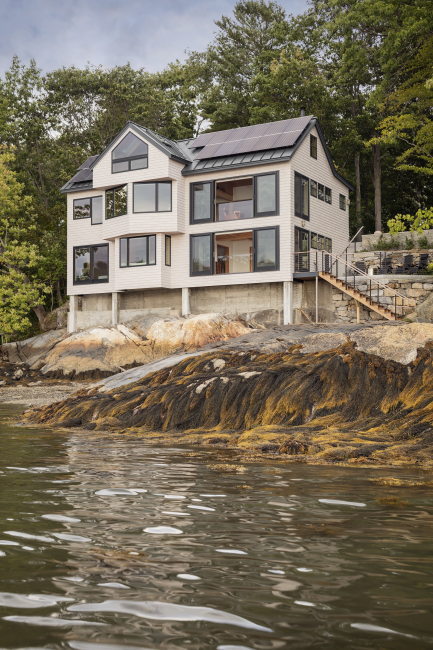 Three story house with solar panels and bay windows on the water