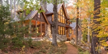 cooper roof, poplar bark shingles, river stone chimney house blends in with environment